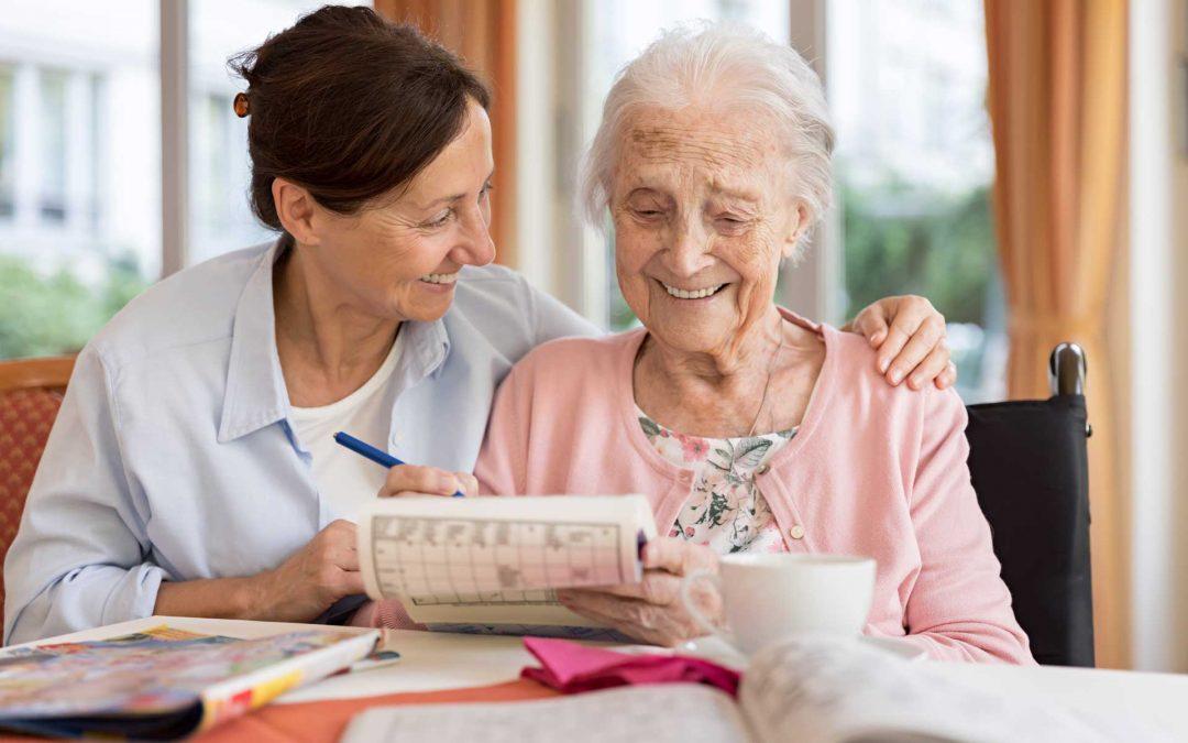Personenbetreuerin mit Kundin beim Zeitunglesen (Foto)