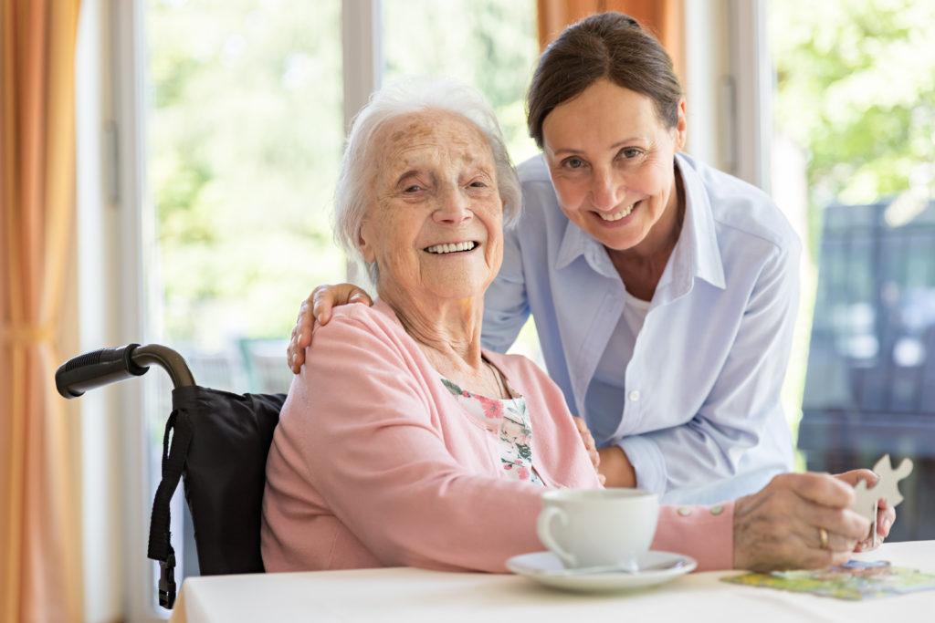 Glückliche ältere Frau im Rollstuhl mit Personenbetreuerin