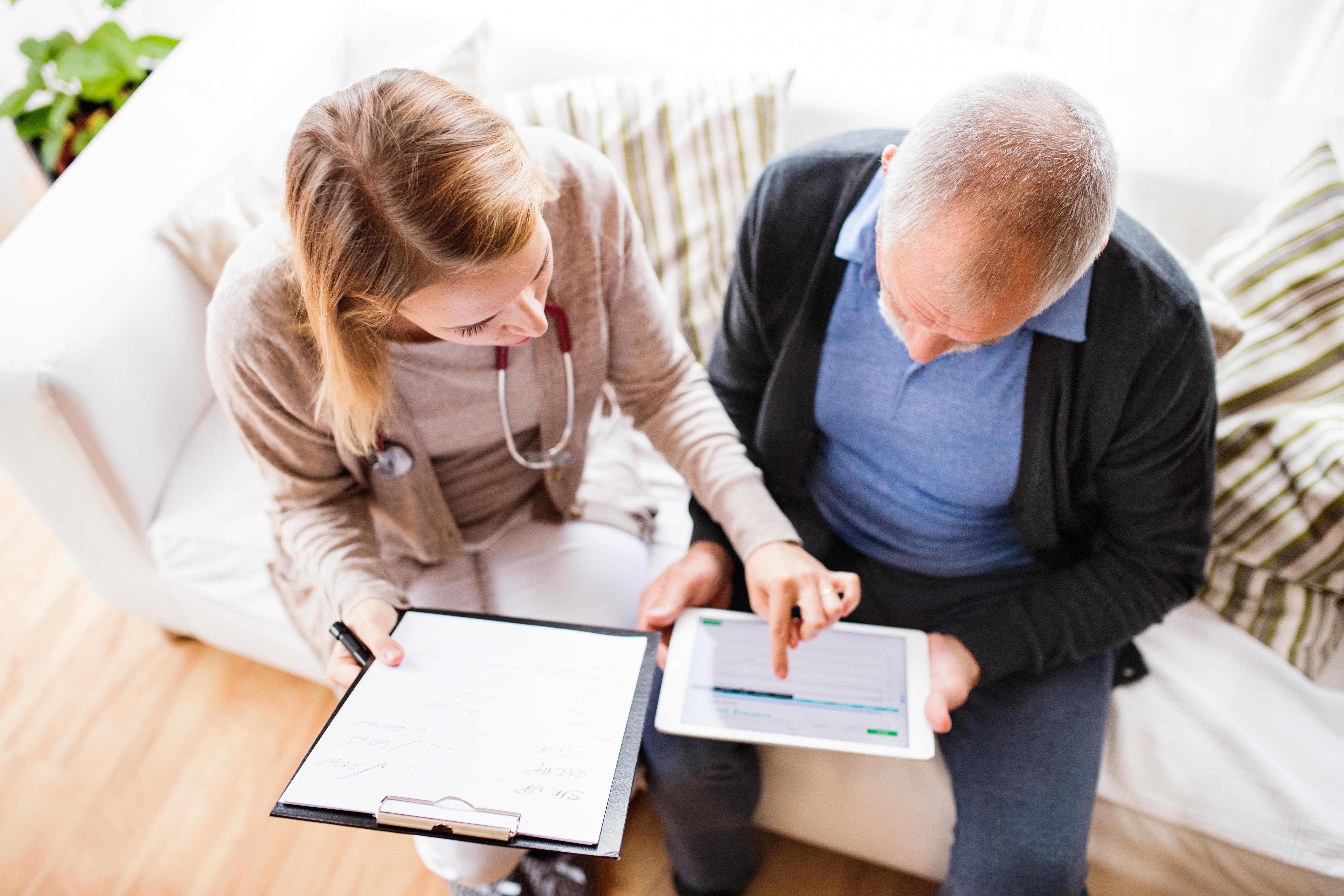 Vermittlungsagentur mit Tablet beim Gespräch mit Senior